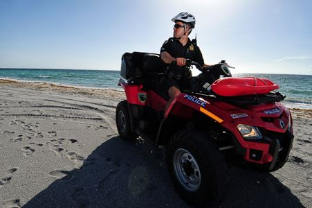 Police Officer Riding an All-Terrain Vehicle at a Beach