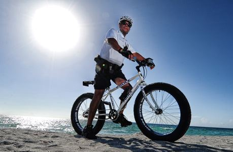 Police Officer Riding a Bicycle at the Beach